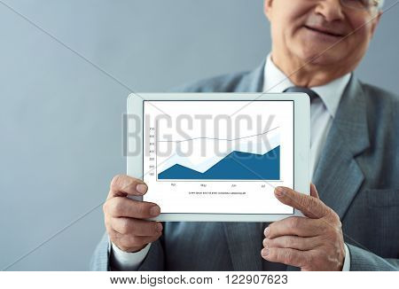 Company growth. Close up shot of old wise man holding tablet with business graph on the screen.