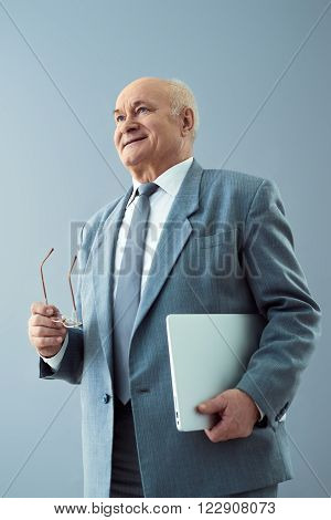 Successful businessman. Nice old man smiling and looking while holding tablet and glasses.