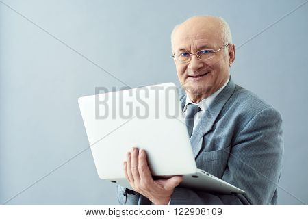 Smart approach. Studio shot of old confident businessman holding laptop and looking wisely while smiling.