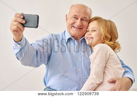 Make selfie very funny. Grandfather and grandchild taking selfie with smartphone in studio, isolated on  white background