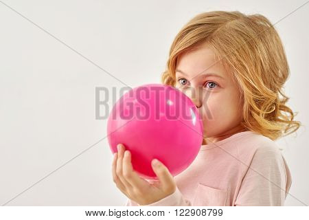 Happy childhood. Little girl carefully inflates balloon, isolated on white background