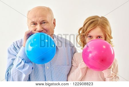 Together more cheerful. Grandfather and granddaughter inflating pink and blue balls in studio on white background.