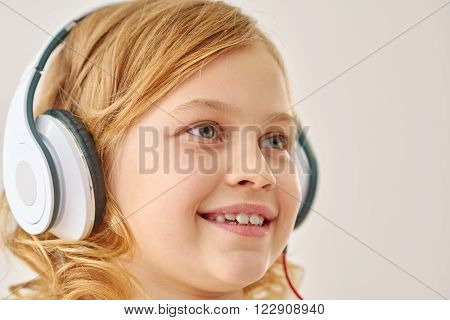 Great songs. Little girl  listening music on her headphones in studio, isolated on white background