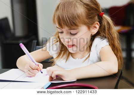 Cute little  preschooler girl is drawing and painting with colorful felt-tip pens at home or kindergarten sitting at small table in the playroom