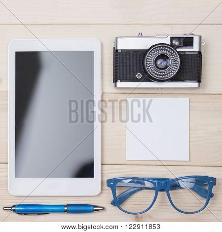 Personal things flat lay. Digital tablet, ball pen, eyeglasses, retro camera and notebook.