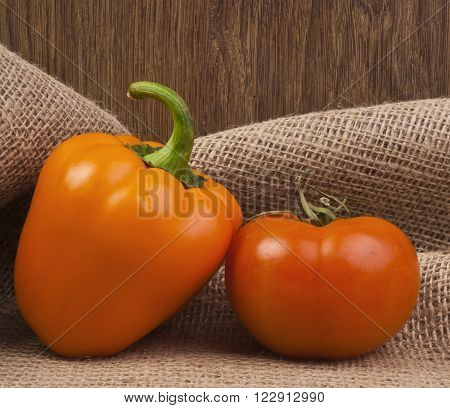 Red tomato and paprika on brown burlap close-up