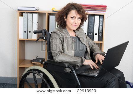 Disabled woman in wheelchair with a laptop working