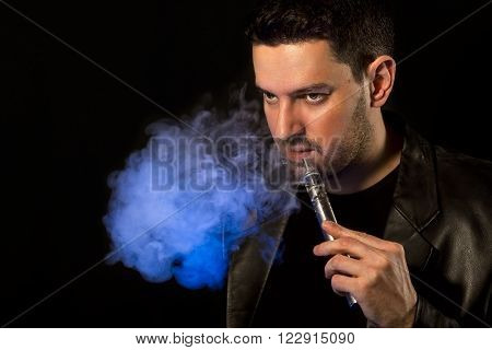 Black haired handsome man vaping e-cirarette custom mod - isolated on black background