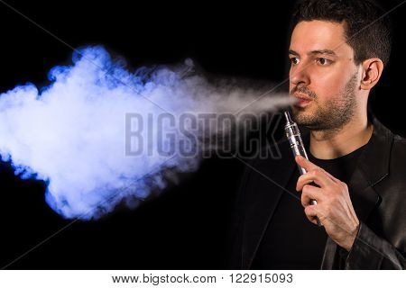 Handsome man vaping e-cirarette mod - blowing cloud of vapor