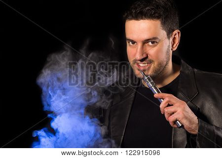 Handsome man smiling with e-cigarette custom mod and vapor - on the black background