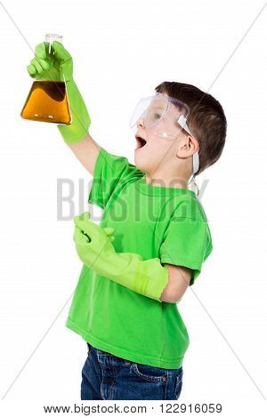 surprised little boy in protective glasses holding a chemical flask with brown liquid, isolated on white