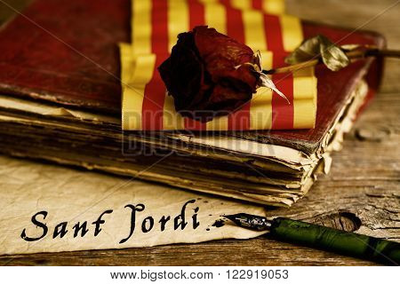 paper with the text Sant Jordi, Saint George Day in Catalan, on a wooden table next to a dip pen, an old book, a rose and a flag of Catalonia, where is tradition to give roses and books in this day