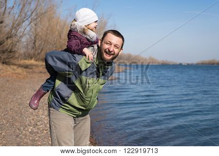 Father playing with his daughter on a riverbank