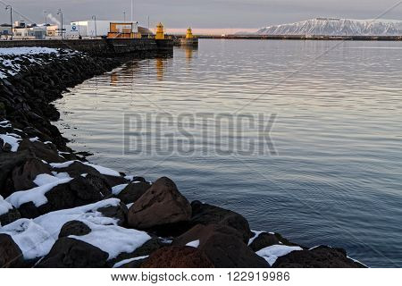 REYKJAVIK, ICELAND, February 26, 2016 : Small yellow lighthouses guard the entrance of Reykjavik old harbour. Reykjavik is the world's northernmost capital of a sovereign state.