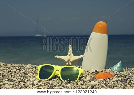 Sunglasses, starfish, seashell, winkle and tanning cream on pebbly beach as symbols of summer vacation. Sea and ship in the background.
