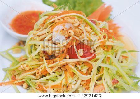 Papaya salad on a white plate. Close-up