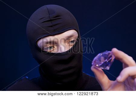 Thief. Man in black mask with a big emerald over dark blue background