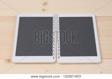 Two digital tablet devices connected with notebook spiral as a concept of opened digital notebook.