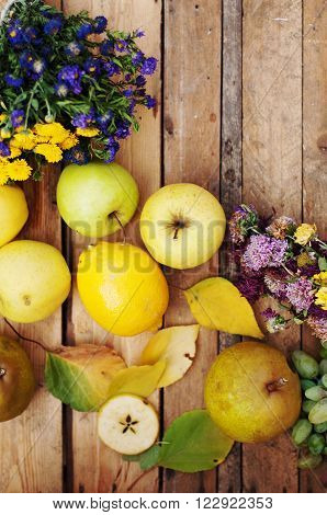 fruit apples pears lemon on a wooden background wildflowers a bouquet of wildflowers autumn food yellow fruits sweet yellow apples autumn harvest leaves view from above