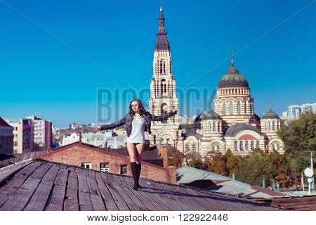Pretty young sexy woman walks on the wooden roof with church behind