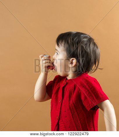 Portrait of a girl using asthma inhaler