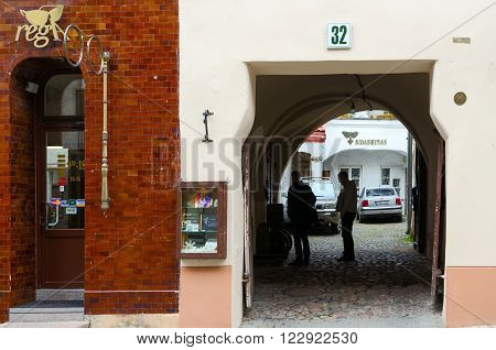 VILNIUS LITHUANIA - JULY 10 2015: Unidentified people are on the street Pilies near the house number 32 in the Old Town of Vilnius. Pilies Street is a popular tourist route with many attractions shops souvenir stores