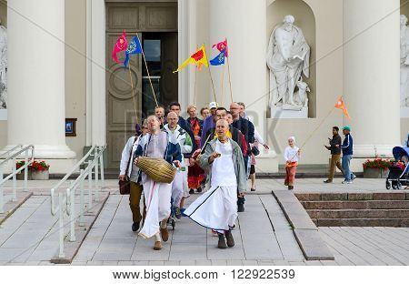 VILNIUS LITHUANIA - JULY 10 2015: Group of Krishnas goes on Cathedral Square of Vilnius near the Cathedral of St. Stanislaus and St. Vladislav
