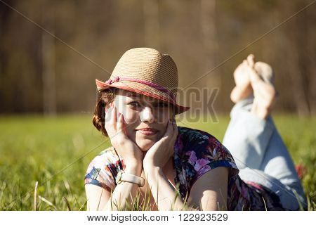 Young smiling woman in sunhat is lying in the grass in sunny summer day.