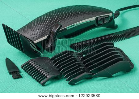 black hair clipper placed on green background.