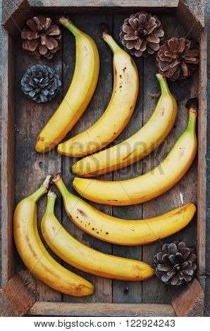 ripe yellow bananas in wicker basket on wooden background view from above yellow fruits yellow bananas in a wooden box food meal vitamins