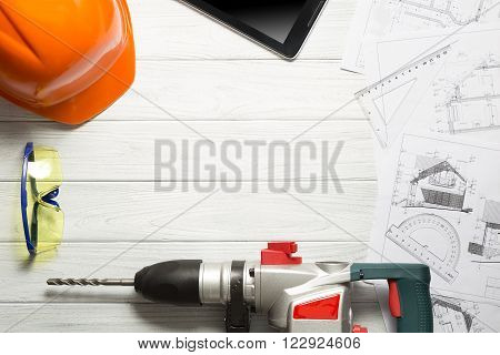 Blueprint on table with helmet drill and safety glasses.
