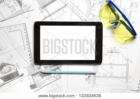 Blueprint on table with tablet and safety glasses.