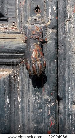a metal hand door knocker on an old black door