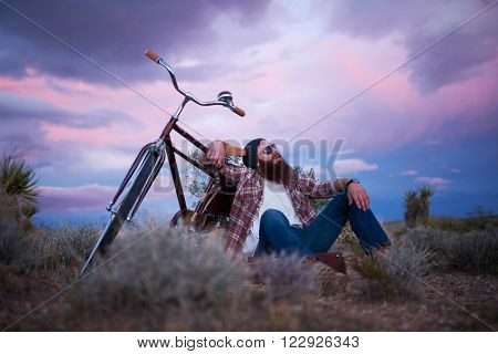 man sitting with bike on suitcase in middle of the desert