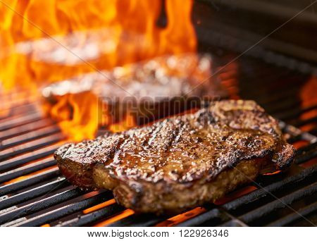 grilling new york strip steaks over flames