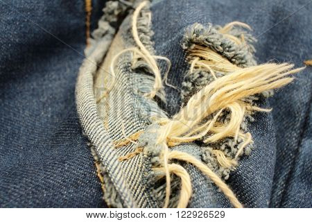 Background or texture of blue torn jeans.