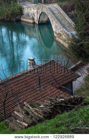 Artificial lake of Pontecosi in Garfagnana in the region of Tuscany railroad bridge and a little church from a stone little bridge