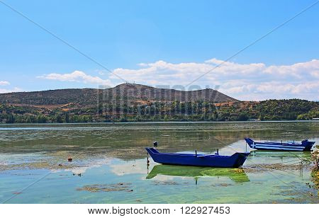 Blue traditional old wooden fishing boats (one is with Greece flag) in the lake Orestiada in Kastoria city of northern Greece