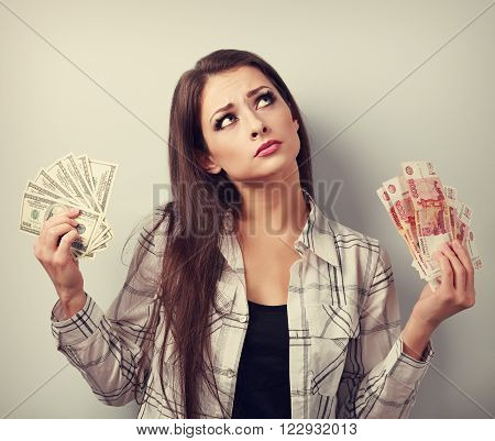 Serious Business Woman Thinking That Currency To Choose, Dollars Or Rubles, Holding Money In Differe