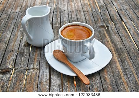 One white cup full of espresso coffee with brown crema on porcelain saucer with small milk jug and wooden spoon on old vintage bamboo table