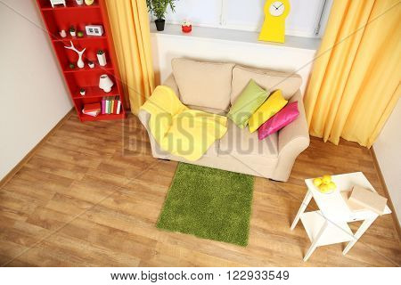 Modern living room interior with beige sofa and small green carpet
