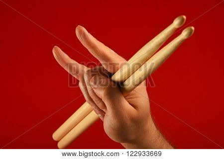 Man Hand With Drumsticks And Devil Horns Over Red