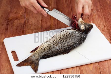Preraring fish - Woman's hands carving a fish with a knife on a white board