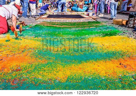 Antigua Guatemala - March 20 2016: Locals decorate handmade dyed sawdust Palm Sunday carpets for procession as spectators watch in colonial town with most famous Holy Week celebrations in Latin America.
