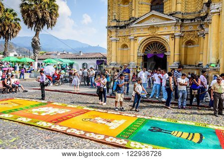 Antigua Guatemala - March 20 2016: Locals & hospital staff admire handmade dyed sawdust carpet outside Hermano Pedro church & adjoining hospital made by hospital staff for Palm Sunday procession in colonial town with famous Holy Week celebrations.