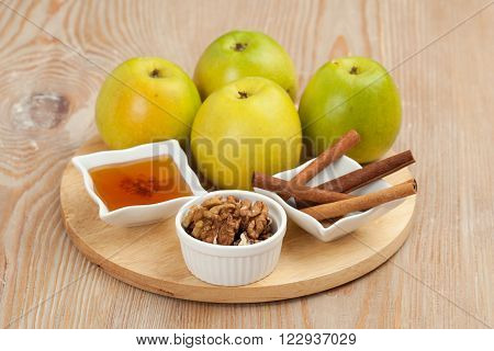 Food. Still life. Apples walnuts honey cinnamonon the wooden board