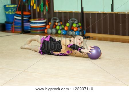 Cute Girl Doing Crafty Trick With Ball On Art Gymnastics Performance
