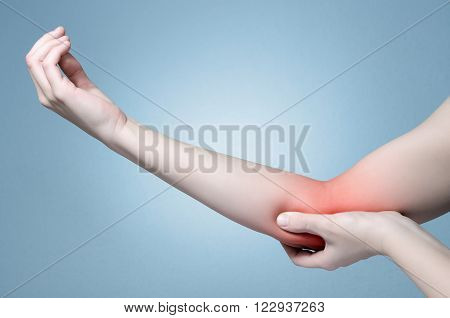 A young woman touching her painful elbow