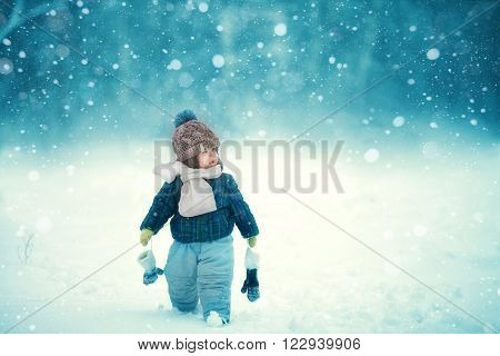 the kid walks in the snow in winter in the white scarf