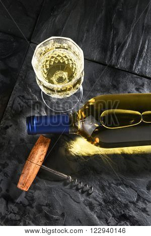 Top View of a white wine bottle laying on its side on black slate. Vertical format with cork screw and wine glass, with copy space.
